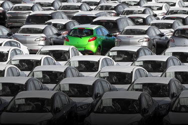 a parking lot of cars in black and white with one green car.jpg