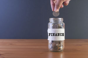 hand dropping quarter into finance jar.jpg